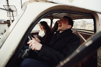 Beautiful and happy woman and man sit in the car