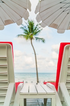 Beautiful beach chairs with umbrella around outdoor swimming poo