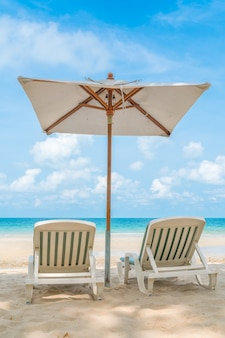 Beautiful beach chairs with umbrella on tropical white sand beac