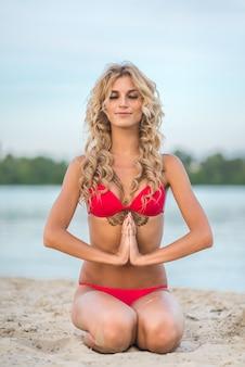 Beautiful blonde girl doing yoga outdoors on the beach