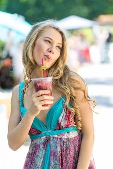 Красивая блондинка девушка пьет сок