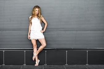 Beautiful blonde girl near gray wall