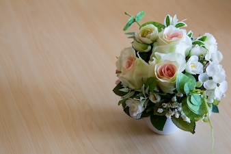 Beautiful bouquet of artificial  flowers in on wooden table