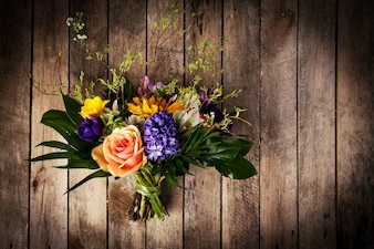Beautiful bunch of flowers on wooden background. Horizontal. View from above.