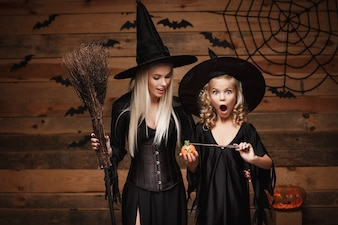 Beautiful caucasian mother and her daughter in witch costumes enjoy using magic with magic wand to halloween pumpkin jar