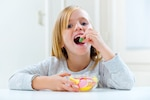 Beautiful child eating sweets at home