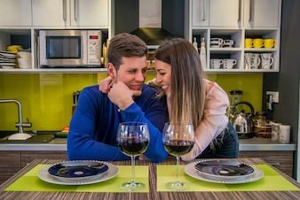 Beautiful couple talking in their pristine home while sitting at kitchen counter. Couple sharing affectionate moment
