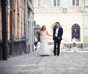 美しいエレガントなカップル、通りを歩く