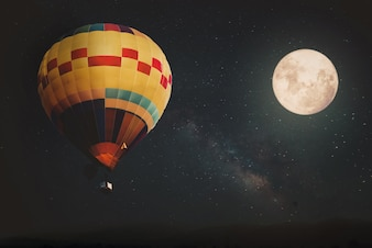 Beautiful fantasy of hot air balloon and full moon with milky way star in night skies background. Retro style artwork with vintage color tone