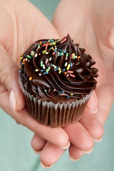 Beautiful feminine hand holding tasty appetizing chocolate cupcake. Blue Background. Closeup.