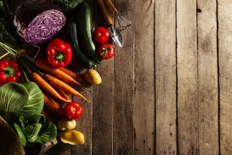 Beautiful fresh harvest vegetables on wooden table with straw hat. Farm, agriculture, spring or summer concept.