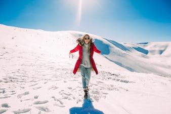 太陽を楽しむ美しい少女、山の中の冬の日