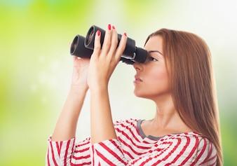 Beautiful girl looking through binoculars
