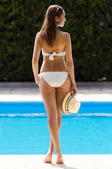 Beautiful girl posing at the swimming pool.