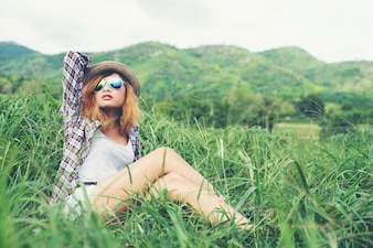 Beautiful hipster woman sitting in a meadow with nature and moun