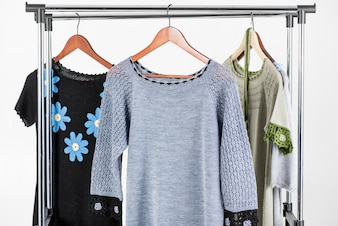 Beautiful knitted dresses hanging on a hanger on a light background