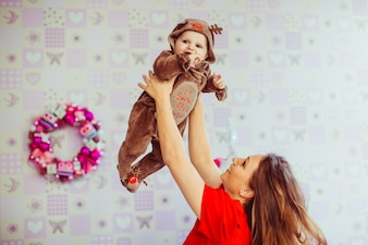 Beautiful mom throws her lovely son in the air
