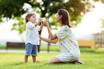 Beautiful mother gives child a drink of water in the park.