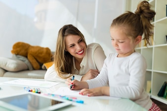 Beautiful mother with her daughter drawing with crayons at home.