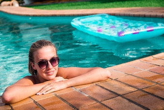 Beautiful natural woman smiling in pool on summer vacations. Young female model in bikini.