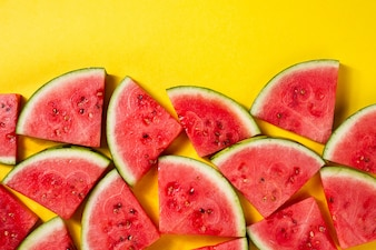 Beautiful pattern with fresh watermelon slices on yellow bright background. Top View. Copy Space.