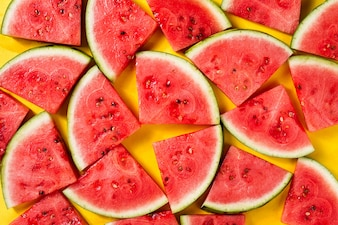 Beautiful pattern with fresh watermelon slices on yellow bright background. Top View.