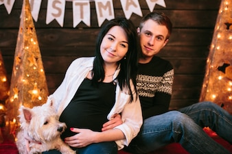 Beautiful pregnant couple with dog