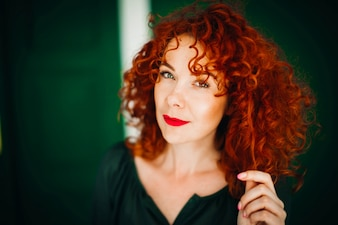 Beautiful red-haired woman sitts on a green background