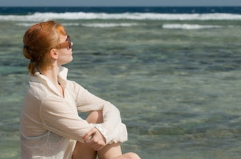 Beautiful red woman relaxing by the ocean