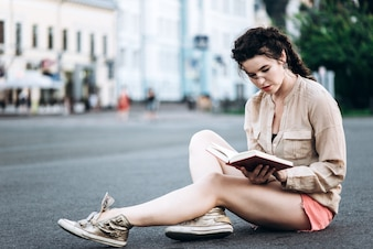 Beautiful student girl reading a book while sitting on the asphalt in the middle of the street