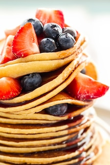 Beautiful Tasty Appetizing Stack Pile of Pancakes with Fresh Summer Fruits and Syrup. Closeup. Bright Background.