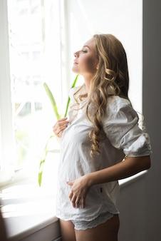 Красивая женщина в белом шелковом халате, стоя рядом с окном