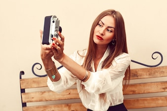 Beautiful woman playing with her vintage camera