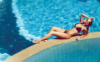 Beautiful woman relaxing in the pool in summer