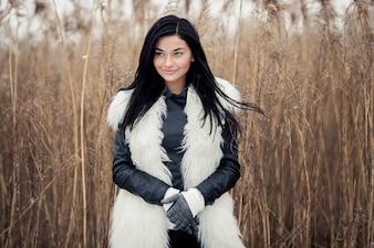 自然の中でコートを持つ美しい女性