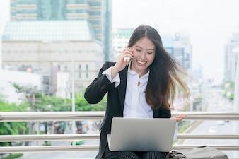 ラップトップとドアで働くことを笑わせている美しい若いビジネス女性