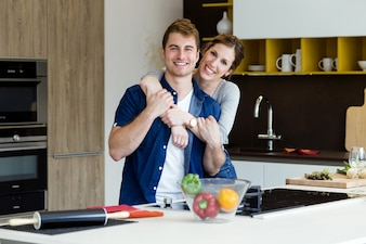Beautiful young couple looking at camera in the kitchen at home.