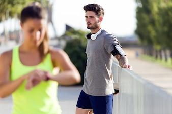 美しい若いカップルは通りで走った後にリラックスします。