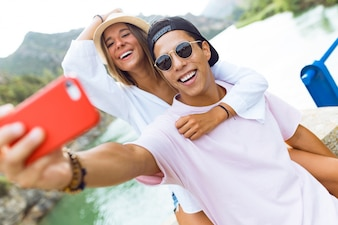 Beautiful young couple taking a selfie in the mountain.