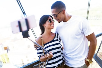 Beautiful young couple taking a selfie in the street.