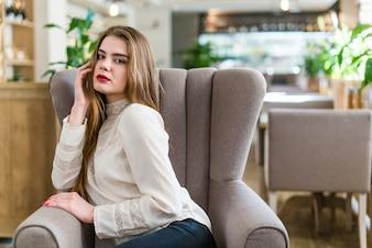 Красивая молодая девушка с профессиональной макияж и прическа, сидя в ресторане.