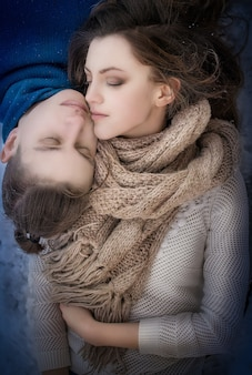 Beautiful young man an woman lean to each other faces lying on the snow