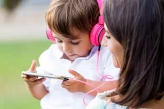 Beautiful young mother with her son listening to music in the park.