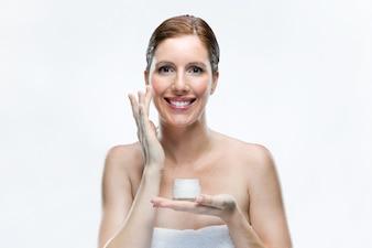 美しい若い女性は、白い背景の上に顔に化粧品クリームを適用する。