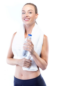 Beautiful young woman drinking water after doing exercise over white background.