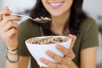 Beautiful young woman enjoying breakfast at home.
