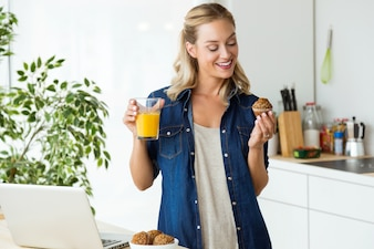 Beautiful young woman having breakfast in the kitchen.