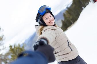 美しい若い女性は、冬の背景を楽しむ。