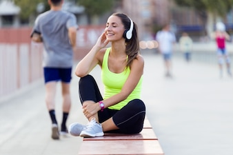 Beautiful young woman listening to music in the street.