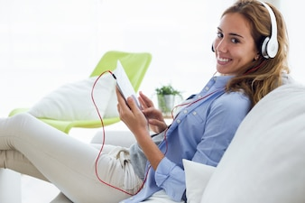 Beautiful young woman listening to music with digital tablet at